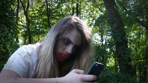 Creepy Zombie Woman on a smartphone in the woods