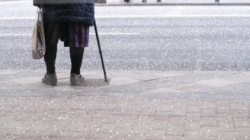 Elderly woman is waiting near the road waiting for the car under a strong hail