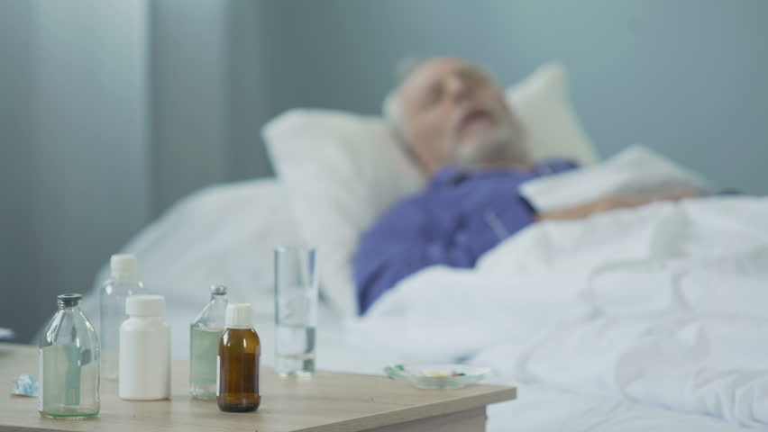 Terminally ill man taking painkillers and sleeping in hospital ward, suffering