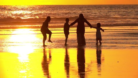 SLOW MOTION, CLOSE UP: Silhouetted Muslim family holding hands standing on dreamy sandy Kuta Beach in Bali watching splashing ocean at golden light sunset. Arab mother and children watching sea waves