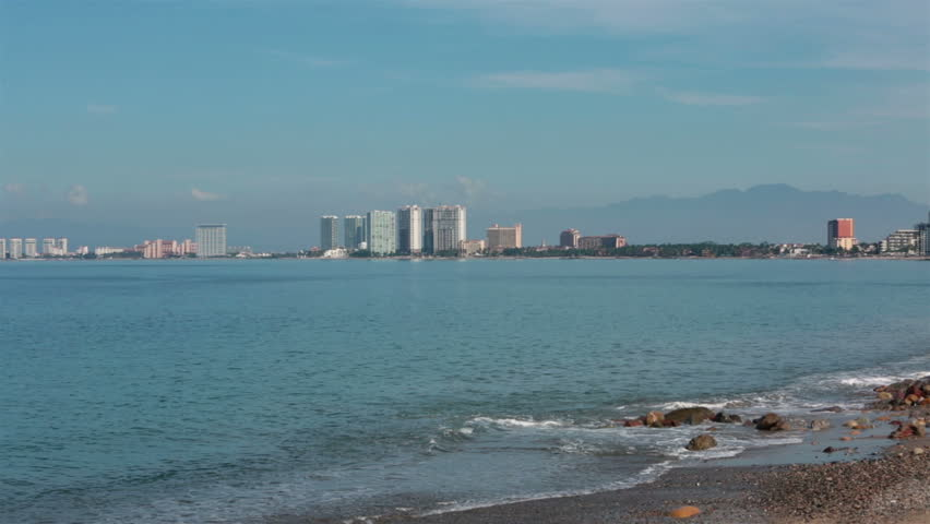 Puerto Vallarta across Banderas Bay beach surf. Boardwalk and Malecon beach and tourist area on shore of Pacific Ocean. Cultural and artistic center of city with many abstract and modern sculptures.