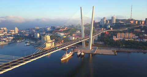 Panoramic aerial view of impressive Golden Bridge (cable-stayed, built in 2012) across the Golden Horn harbour and morning Vladivostok city is on the background. Russia. Autumn