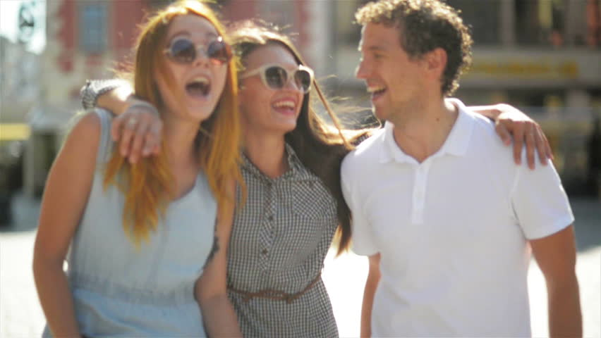 Happy Meeting of Three Friends Hugging in the Street During Warm Summer Day. Two Girls Wearing Sunglasses and Short Dresses and Handsome Boy in White Shirt and Jeans Smiling and Embracing Outdoors.