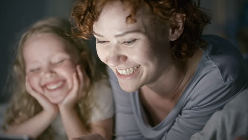 Tilt up of happy young mother with short curly hair lying on bed and holding tablet: she reading funny story to laughing boy and girl