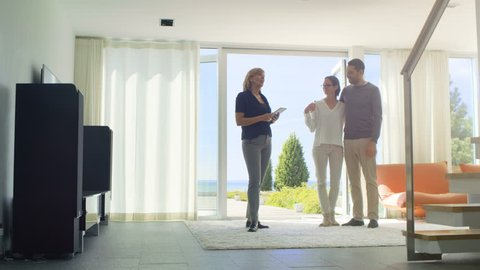 Real Estate Agent Shows Smart House Controlled with Tablet Computer to a Beautiful Young Couple. House Has Floor to Ceiling Windows and Seaside View. Shot on RED EPIC-W 8K Helium Cinema Camera.