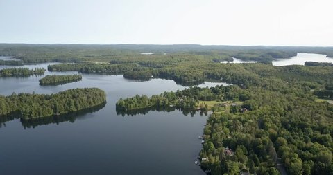 Aerial Drone footage, flying forward over a secluded lakes surrounded by dense forest, cottages can be seen.  Sky and clouds reflected in the water.