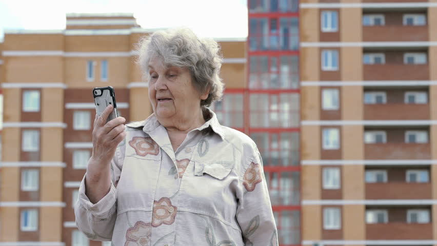 Old elderly woman dressed in a cotton shirt standing on the background the brick multi-family building talks with a relatives using a silver smart phone.