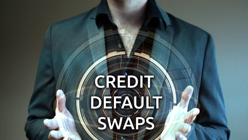 A businessman holds up a futuristic glowing aura reading Credit Default Swaps | Shutterstock HD Video #30731767