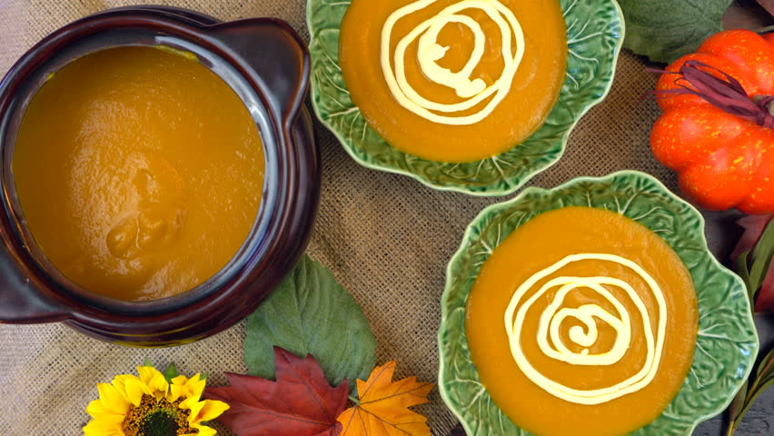 Serving hot pumpkin soup into green leaf bowls and making spider web cream decorations, on a rustic background for Happy Halloween party food, time lapse.