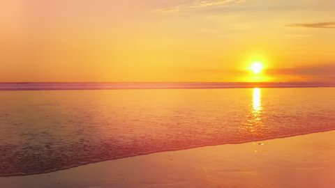 CLOSE UP: Gentle crystal clear swash wave traveling up the seashore washing beautiful sandy beach at gorgeous golden light sunset. Yellow sun setting behind the ocean horizon. Stunning tropical beach