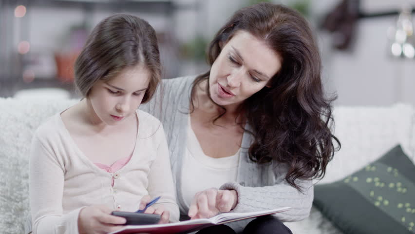 Caucasian mother with natural beauty helps her daughter to do her homework. In slow motion