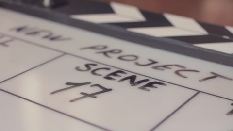 Male hand erasing scene number on movie clapperboard