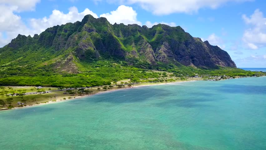 Aerial Scenic flyover footage of ocean of Chinamans Hat, Oahu Hawaii.  Tropical view of Kualoa Valley, Koolau Mountain. Kaneohe Bay side. Turquoise-blue water lovely with blue sky. 4K UHD drone shot.   Shutterstock HD Video #30760309