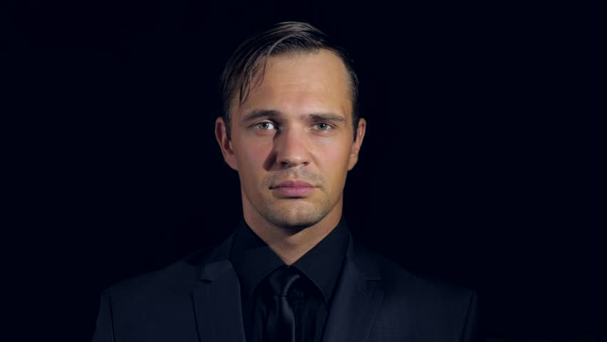 closeup of a man in black clothes on black background. 4k. Slow motion. man strokes his chin and looks at the camera. decision-making gesture