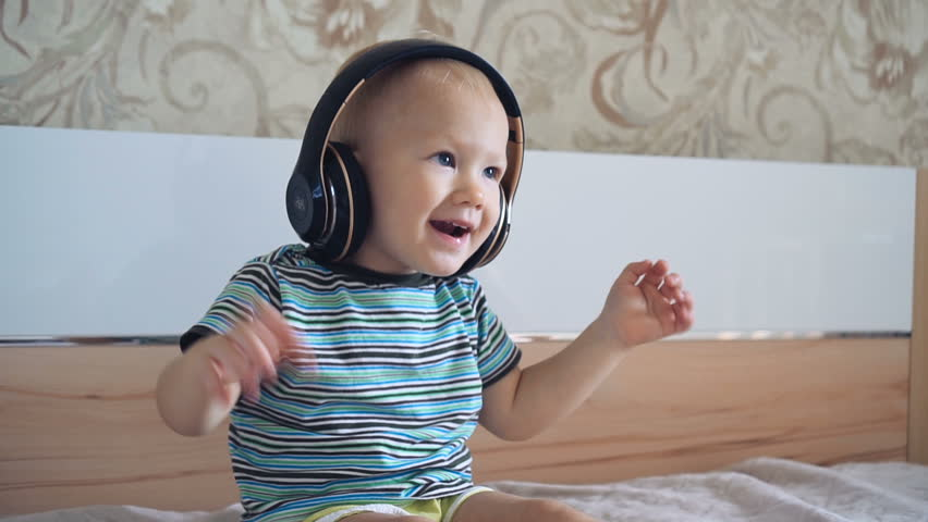 Little boy listens to music on headphones and dances