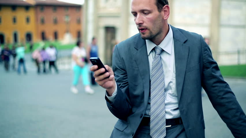 Business man in tourist city checking cell phone for new messages