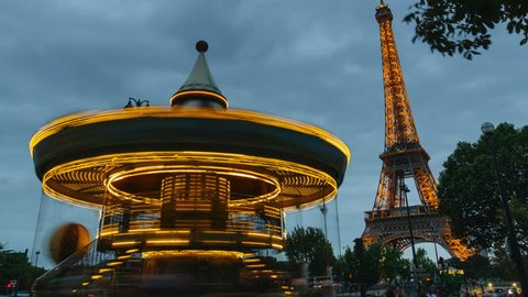 Paris - AUG 2017. Time lapse of illuminated merry-go-round and Eiffel Tower at night, symbol of Paris and famous landmark in France. Famous touristic places and romantic travel destinations in Europe