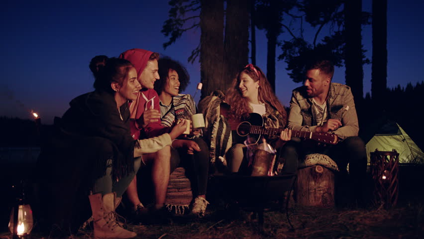 Diverse Group Of Attractive Young People Playing Guitar And Singing Around Forest Camp Fire Drinking And Clapping Close Friendship Tourism Romantic Musical Getaway Concept Slow Motion Shot On Red Epic #30848377