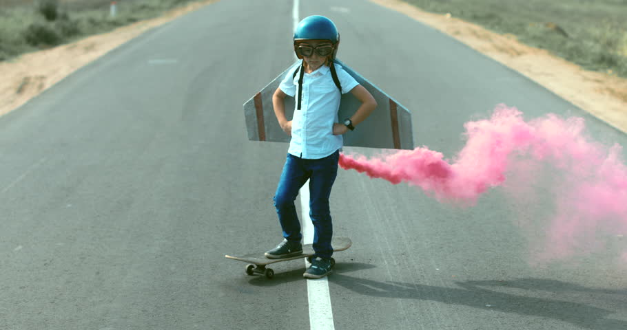 Little boy wearing helmet and styrofoam wings standing on a skateboard on a rural road, pretending to be a pilot. 4K UHD RAW edited footage | Shutterstock HD Video #30869167
