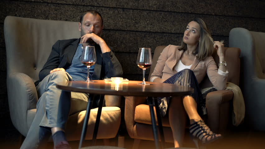 Bored, offended couple drinking wine sitting in cafe