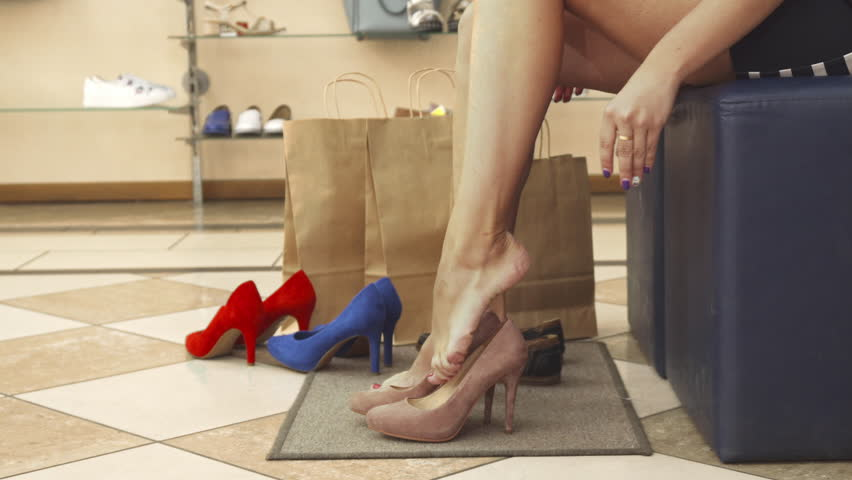 Woman trying the shoes on. She uses her finger as a shoehorn. We only see her legs. Shoot in a shoe shop | Shutterstock HD Video #30874621