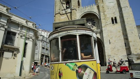 Lisbon, Portugal - August 25, 2017: Historic tram 28 line in front of Lisbon Cathedral in Alfama district. Lisbon street with yellow vintage tram and Se de Lisboa. symbols of the Portuguese capital.