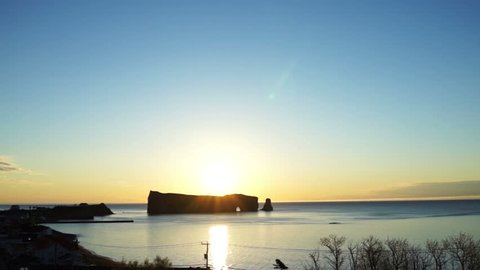 Famous Rocher Perce rock in Gaspe Peninsula, Quebec, Canada, Gaspesie region at sunrise and sun reflection path, flare, glade and warm soft sunlight