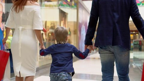 The boy holds a hand from the mother and the father. Parents not Sousse packages with Christmas gifts. Family Christmas shopping. The boy with parents go along the corridor shopping center. Christmas