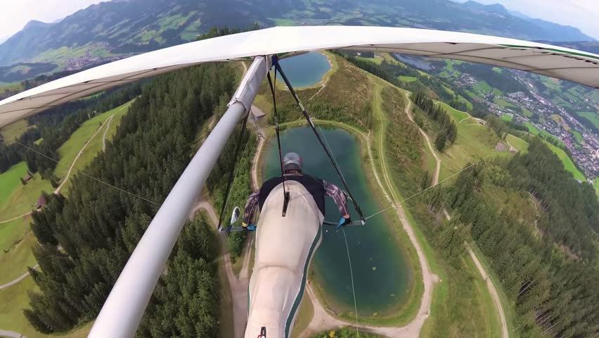 Kitzbuhel, Austria - 25 August 2017. Hang glider pilot speeds up over lake in  famous Kitzbuhel ski resort in summer during Austria Open competition. Onboard video in 4K taken with action camera.