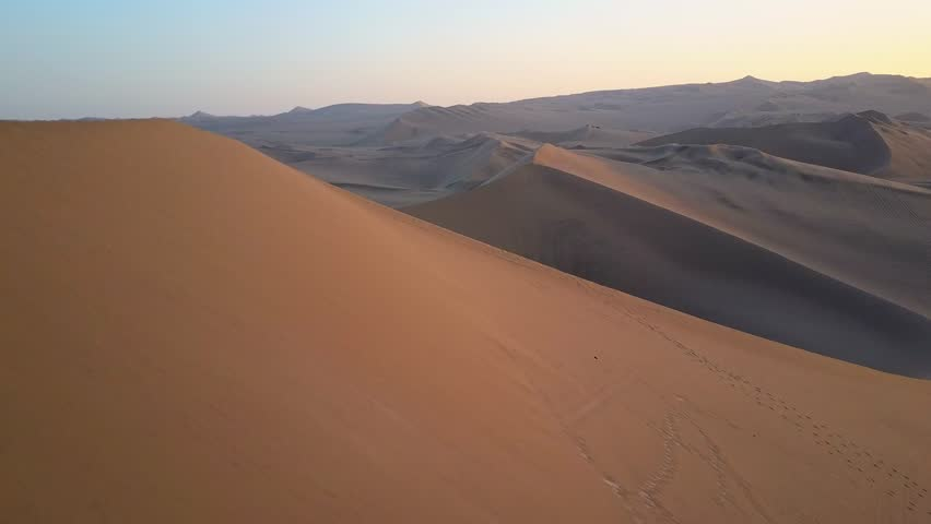 Aerial drone footage on a sunny day above sand dunes of Peru. Close to Ica and Huacachina. Similar to Sahara and Emirates Deserts. Boogie cars driving and people sandboarding. Oasis nearby. | Shutterstock HD Video #30910507