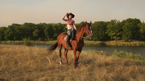 Sexy girl posing to the camera on horse at sunset by the lake.