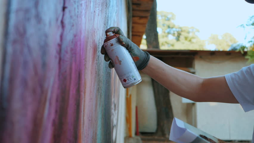 Street artist painting colorful graffiti on generic wall - Modern art concept with urban guy performing and preparing live murales with red aerosol color spray. Slow motion. | Shutterstock HD Video #30926761