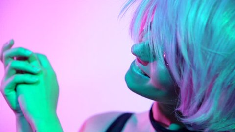 Disco girl dancing on party. Fashion model woman in colorful bright lights, beautiful girl with trendy make-up and haircut. Colorful make up. Over colourful vivid background. 4K UHD slow motion video