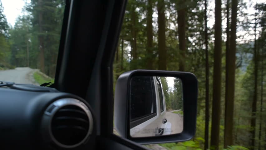 SUV driving through forest in mountains | Shutterstock HD Video #30933493