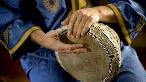 Tight shot of man in Moroccan dress playing arabic doumbek, darbuka, or