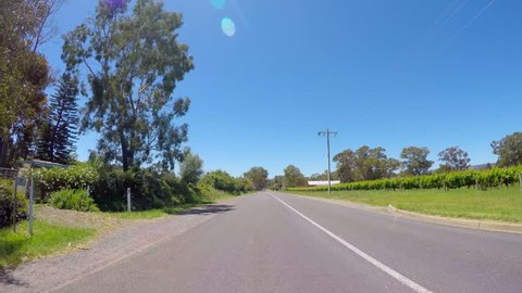 Vehicle POV past Kangaroo Crossing sign on country road, taken in McLaren Vale winery region, South Australia, with sun reflections and lens flare.