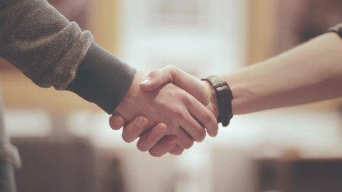 Handshake of two men. Friendly man shaking hands. Close up of men greeting with handshake. Business partners handshaking
