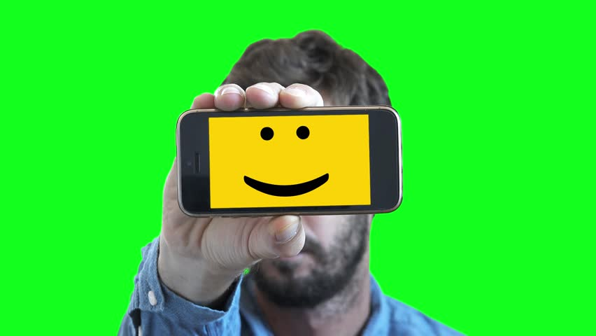 Happy Man With Smiley Face In Smartphone On Green Screen. Man shows his feelings through a smartphone with a Smiley face on screen | Shutterstock HD Video #30963937