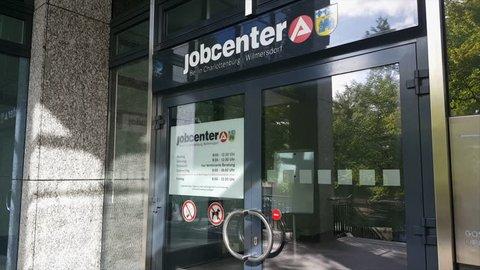 GERMANY - CIRCA SEPTEMBER 2017 - People enter jobcenter Wilmersdorf-Chalottenburg, doors, opening hours sign