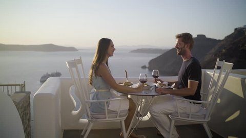 4k travel video honeymoon couple enjoying private dinner at sunset outside on terrace in santorini island overlooking the caldera cheering with red wine