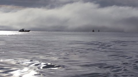 Shooting aft from a moving boat on bright and foggy waters, over ripples in slow motion, watching a small fishing boat adrift, with a larger vessel moving away past the buoy into the fog.