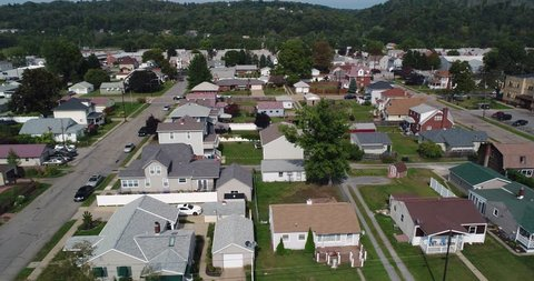 An aerial establishing shot of a typical Western Pennsylvania residential neighborhood in late summer. Pittsburgh suburbs.