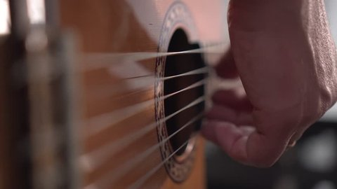 Musician plays acoustic spanish guitar. Close up shot of right hand, shallow depth of field