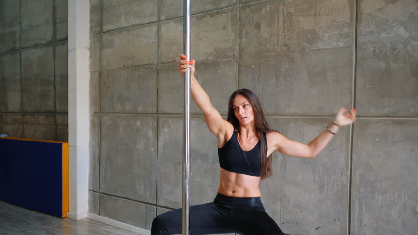 Young sexy slim woman with long hair pole dancing in grey interior.Beautiful,Attractive girl performing pole dance. .Lady with good figure dancing on pylon. 4k