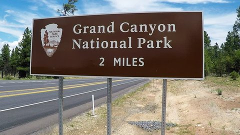 TUSAYAN, AZ/USA: August 1, 2017- Close up shot of a Grand Canyon National Park road sign. Sign gives distance to the entrance of one of the seven wonders of the world.