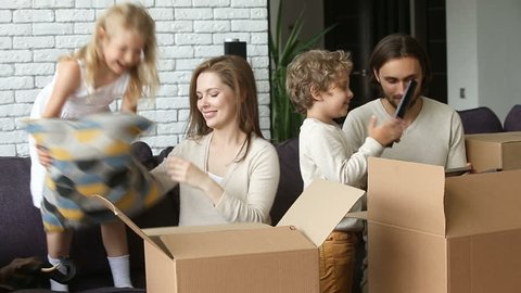 Happy excited family with two children unpacking boxes moving into new home concept, small kids helping parents with belongings in cardboards putting cushion on sofa in living room after relocation