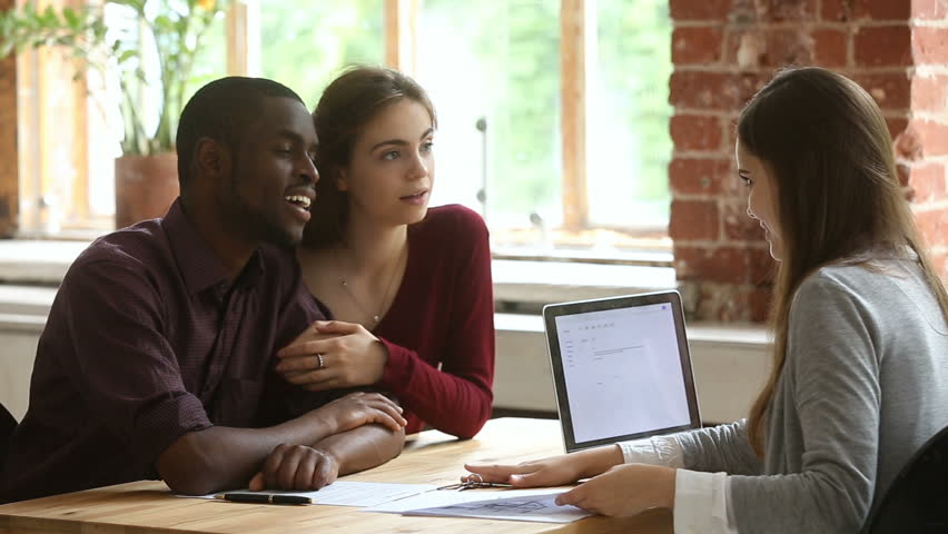 Young multi-ethnic couple planning to buy rent lease new home meeting with real estate agent in office, married diverse family discussing with realtor terms of mortgage loan lending contract | Shutterstock HD Video #31061017