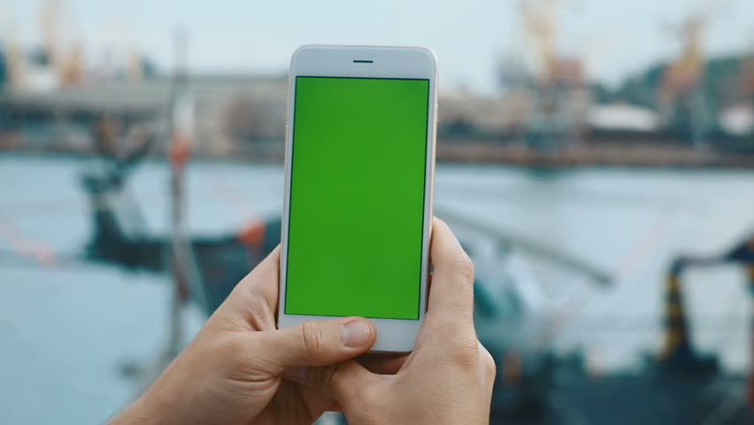 Mans hand shows using holding mobile smart phone outdoor blurred helicopter port background urban evening vertical green screen chroma key tap touch screen network 3g app internet surfing notification | Shutterstock HD Video #31068277