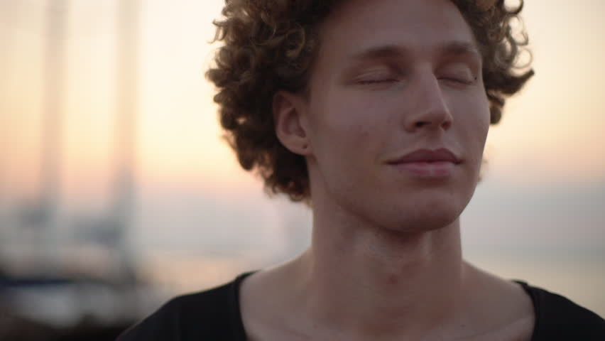 Caucasian curly guy opens eyes smile with affection, evening blue sky. Cloeup, slow motion