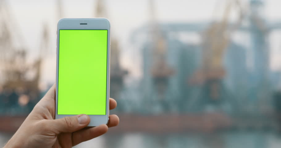 Mans hand shows mobile smart phone blurred background using pointing finger tapping touch screen green chromakey chroma key modern technology development trendy front view outside fog media display